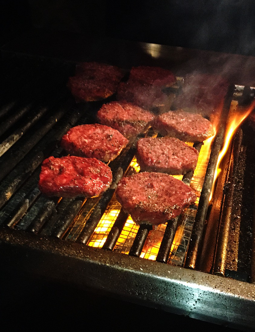 FIRE IT UP! Burgers being flame broiled on the grill.