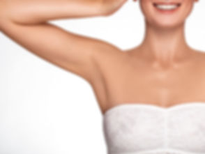 Armpit epilation, lacer hair removal. Young woman holding her arms up and showing clean underarms, d