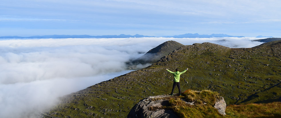 James Forrest, an adventurer, standing above a cloud inversion with his arms in the air on Knockowen mountain in Ireland