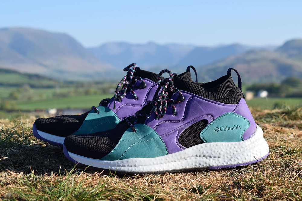 Close up pair of Columbia Men's SH/FT OutDry Mid Shoes in front of a Lake District mountainous background ready for review