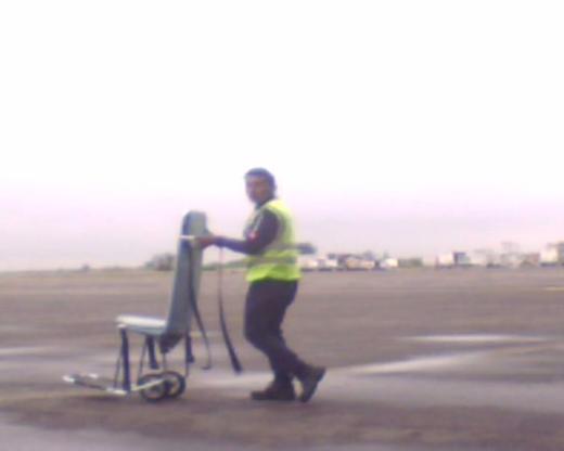 Empleado de Aeropuerto camina empujando una silla pasillera por a zona de aviones