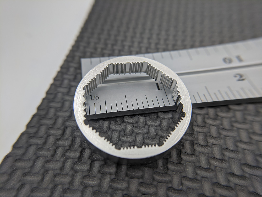 "Stainless steel gear splines, approx 1"" diameter according to pictured ruler. Formed with electrochemical machining."