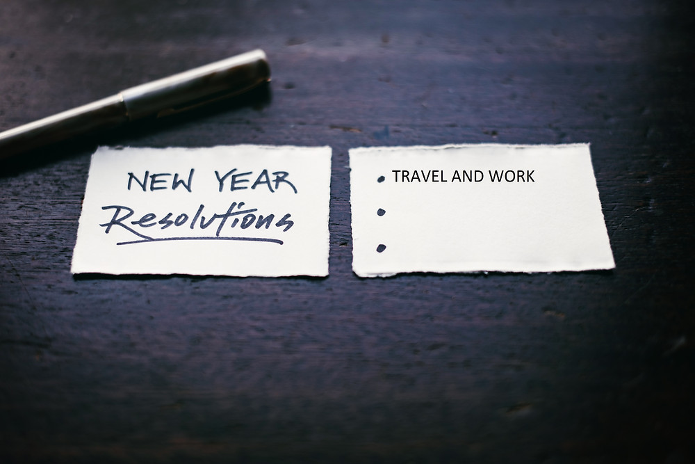 New year Resolutions, Travel and work hard, parchments, pen on a a black rough surface. The colour or writing is Black.