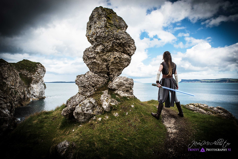 posing on the north coast as rey in cosplay with lightsaber