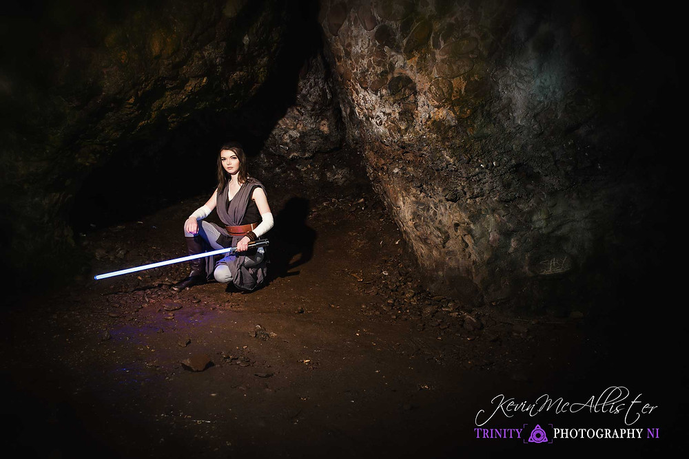 cosplaying Rey of star wars with lightsaber in cave