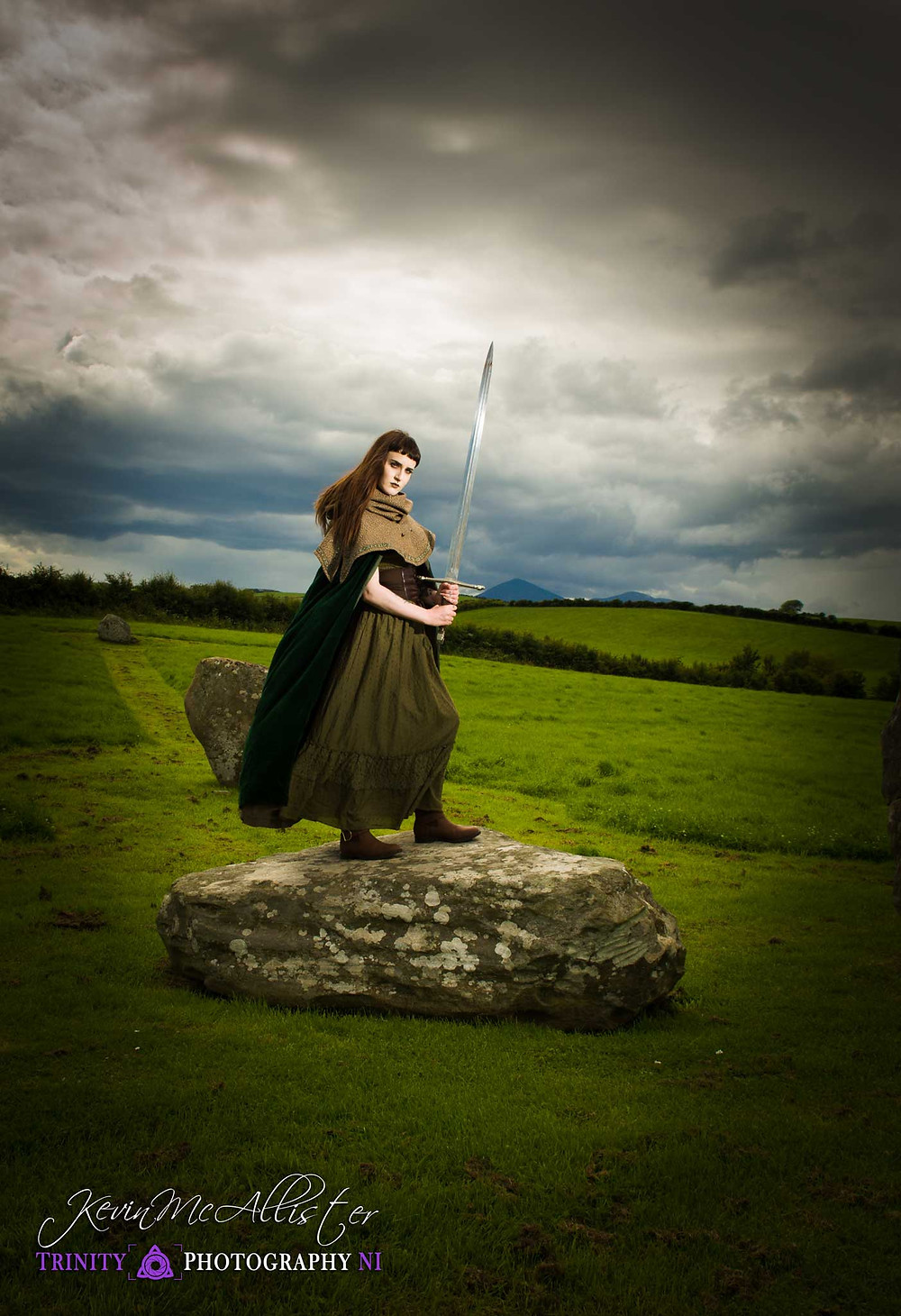 mediaval model standing on a rock with a sword in ireland