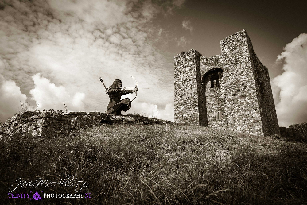 medieval archer draws her boy outside a irish castle