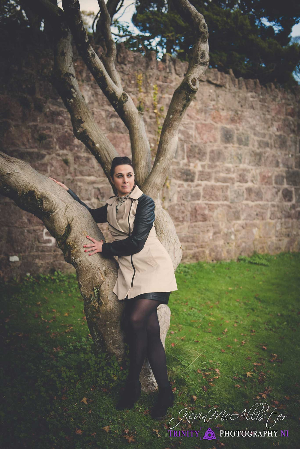 model leaning against a tree with cream Jacket