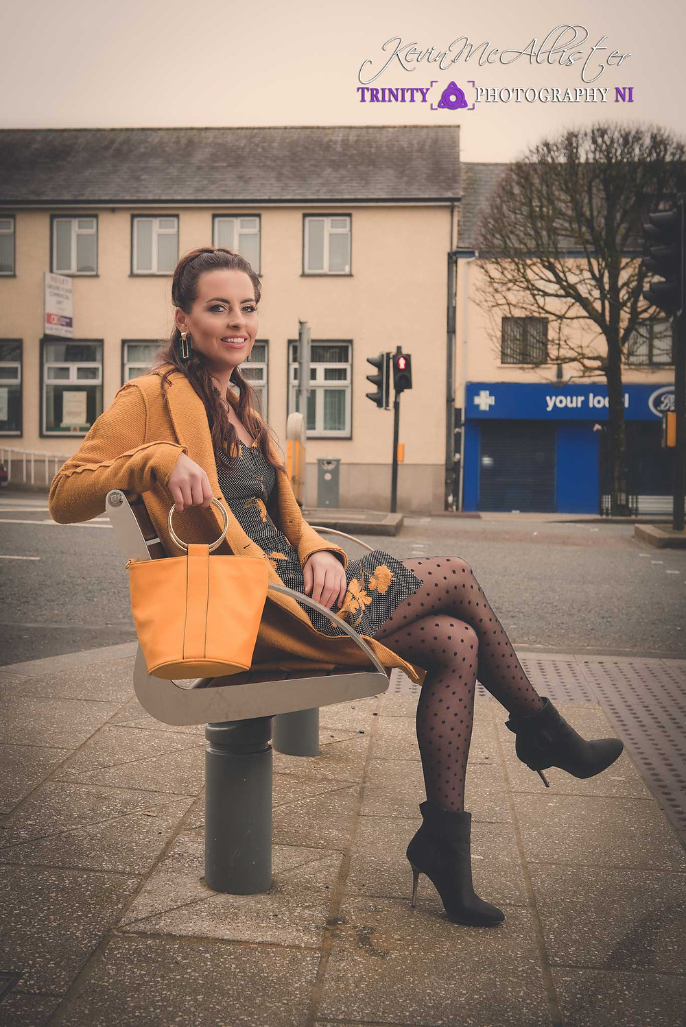 girl sitting at bus stop with handbag