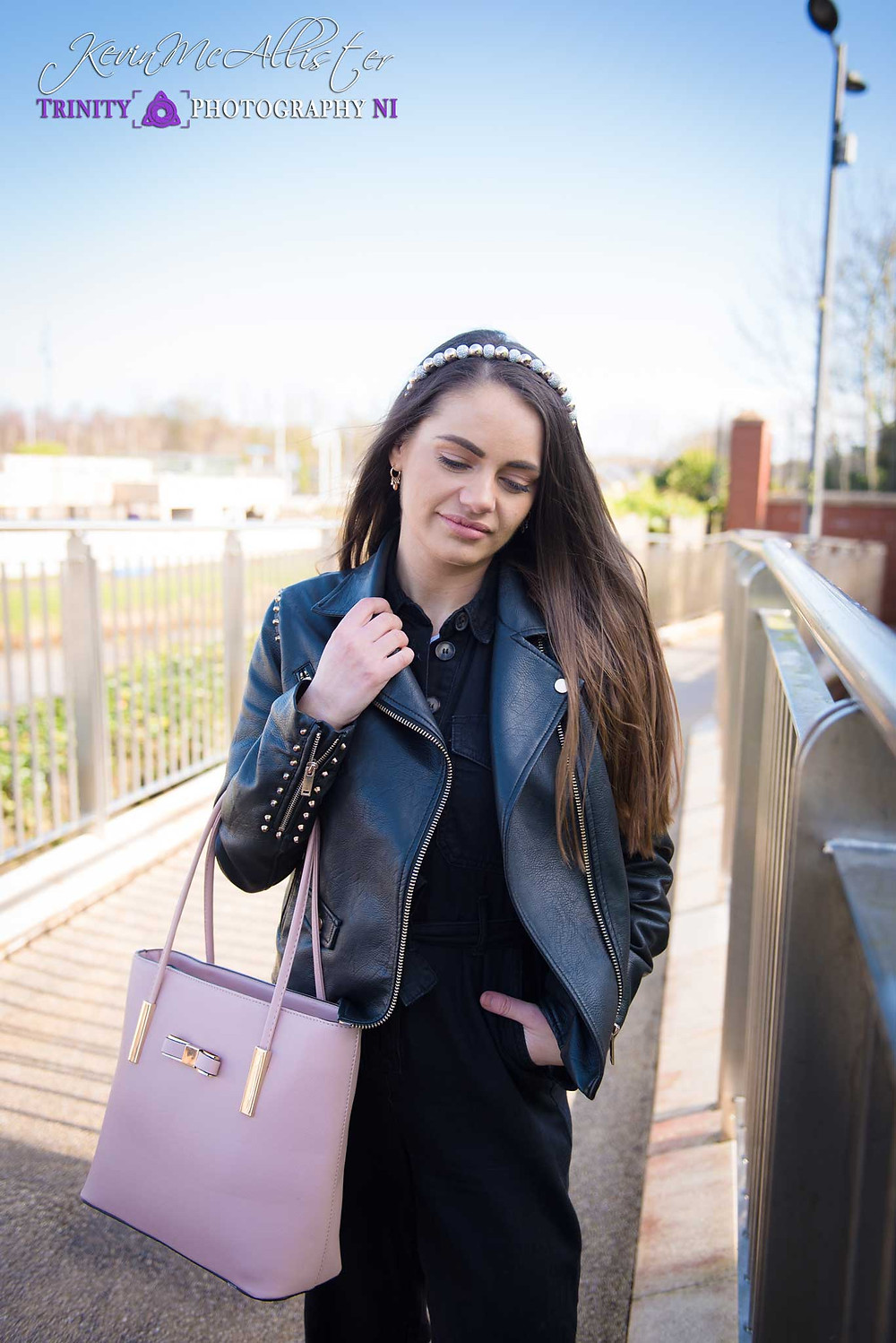 model with black leather jacket and pink handbag, sparkly headband.