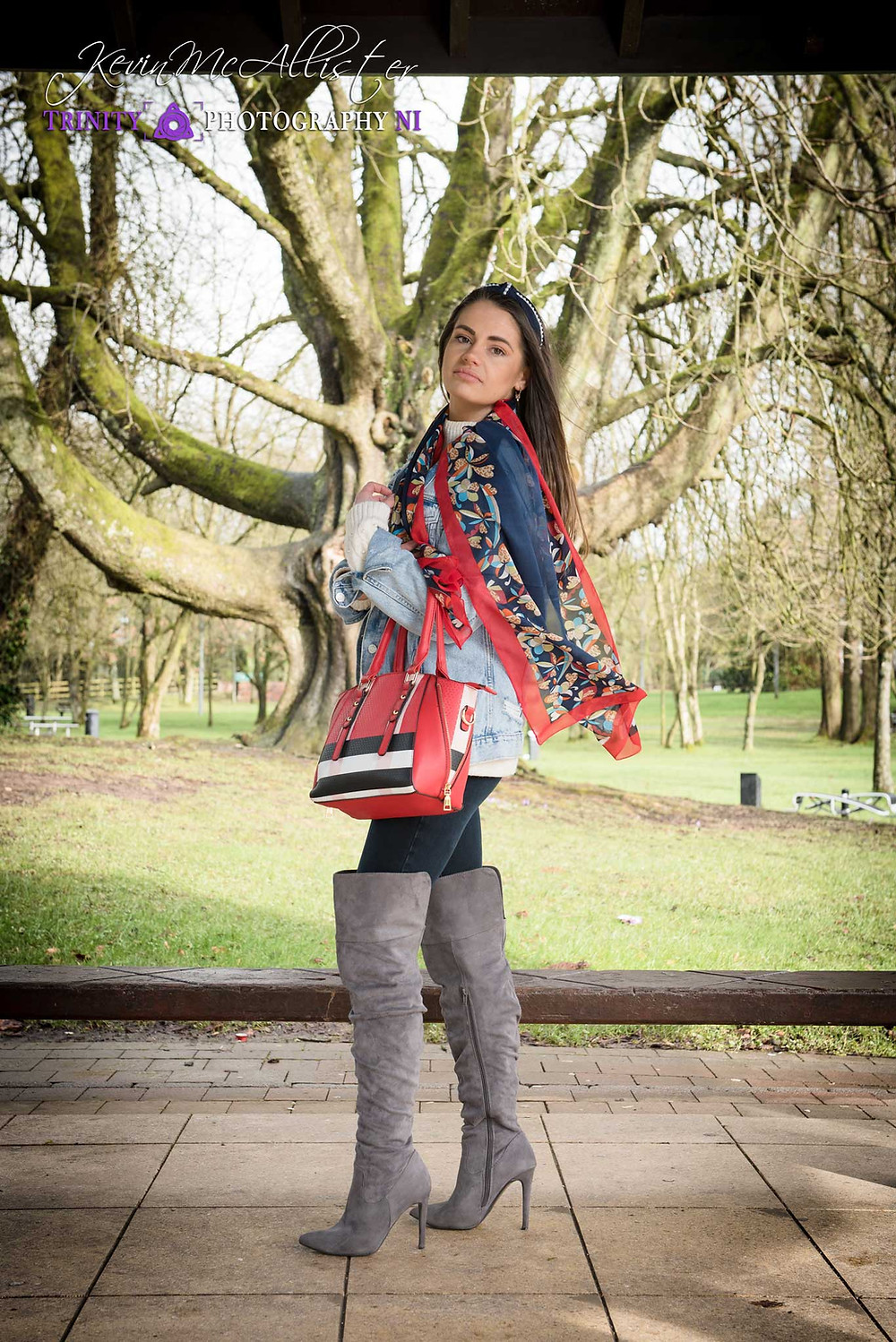 brunette model Knee high grey boots and red bag and scarff