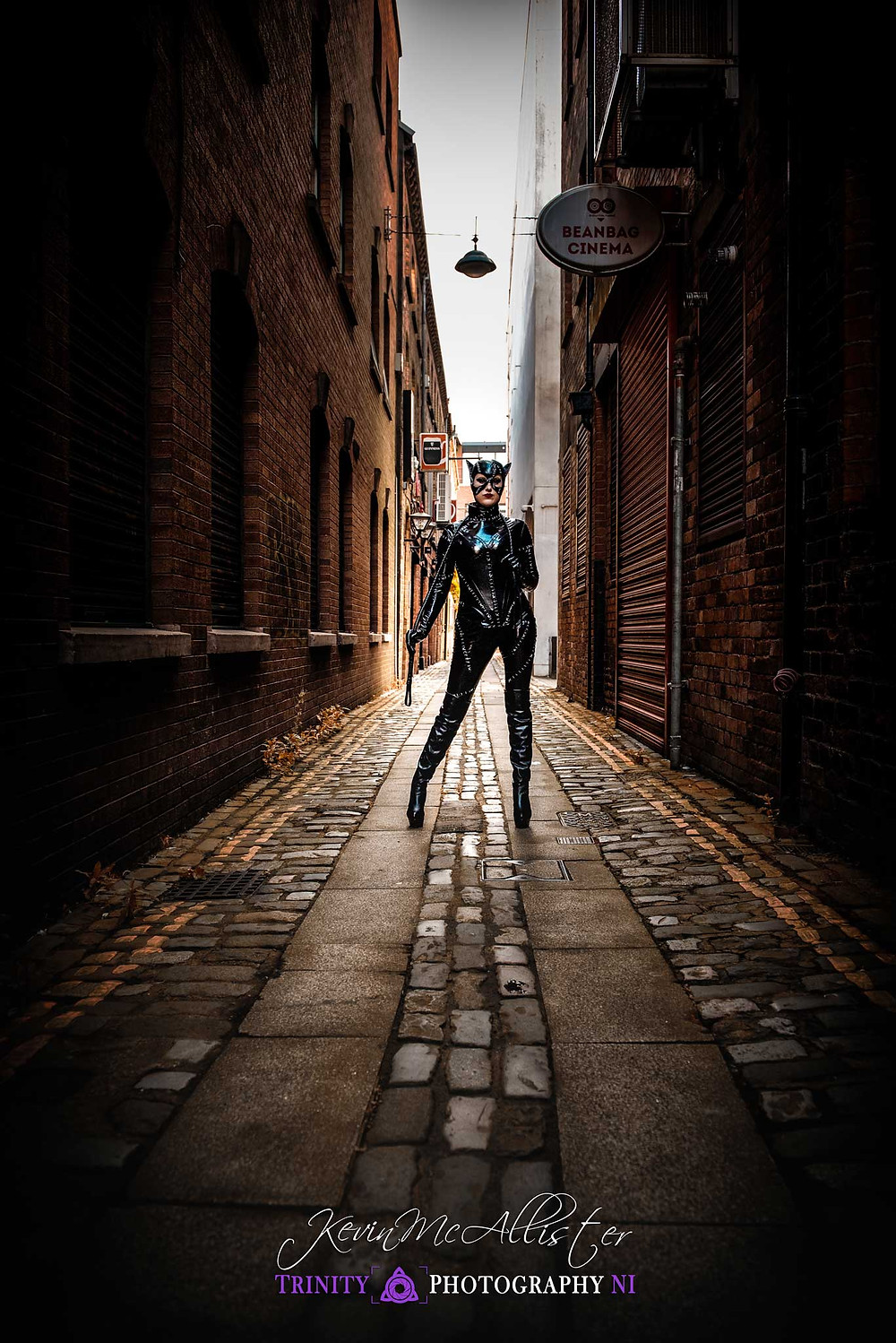 catwoman stands astride the cobblestones on a back alley in belfast