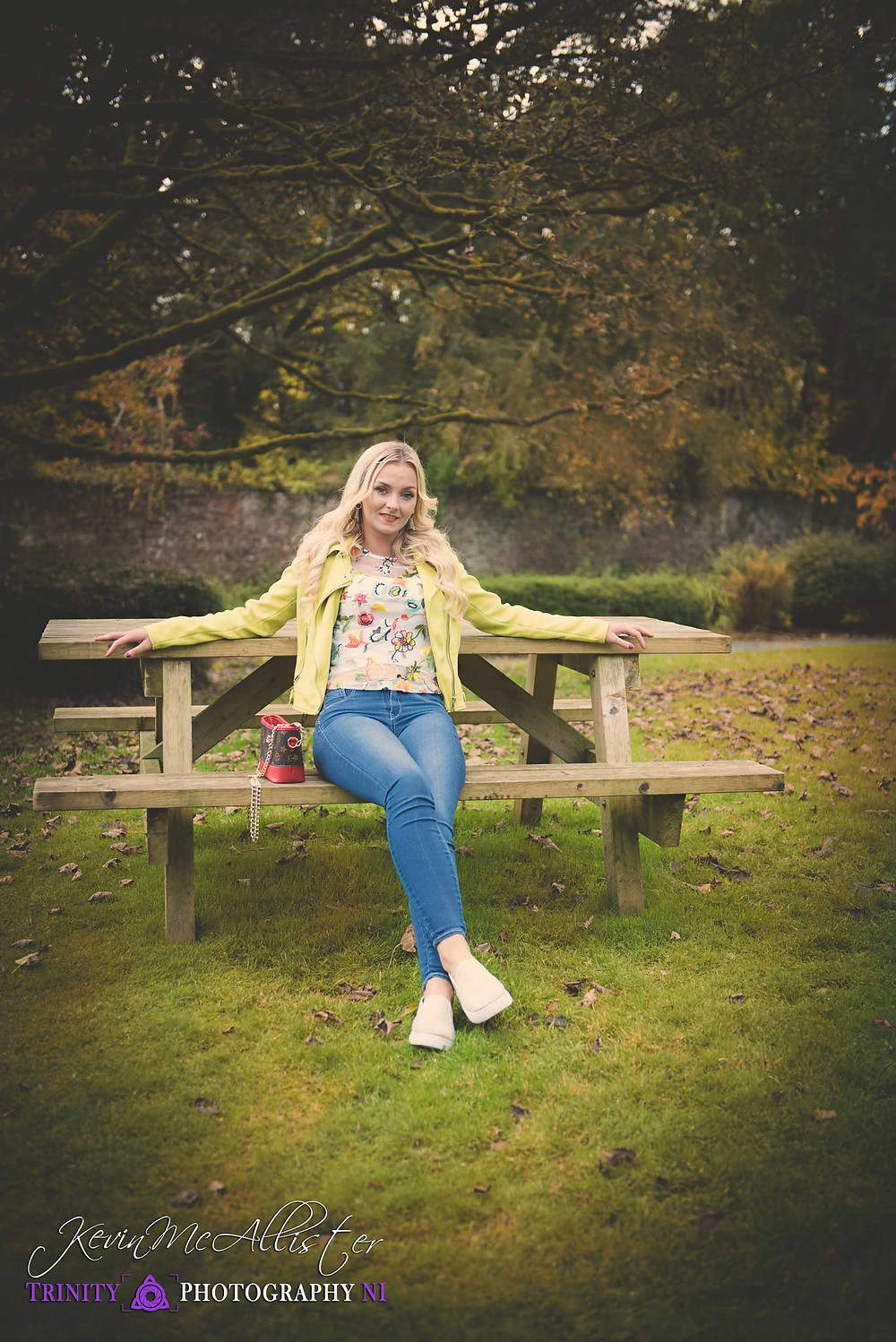 blonde model seated at park bench