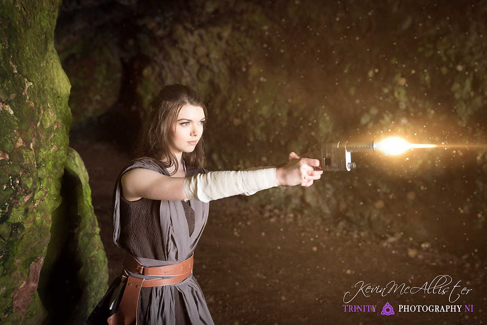 Rey cosplayer fires her gun with sfx