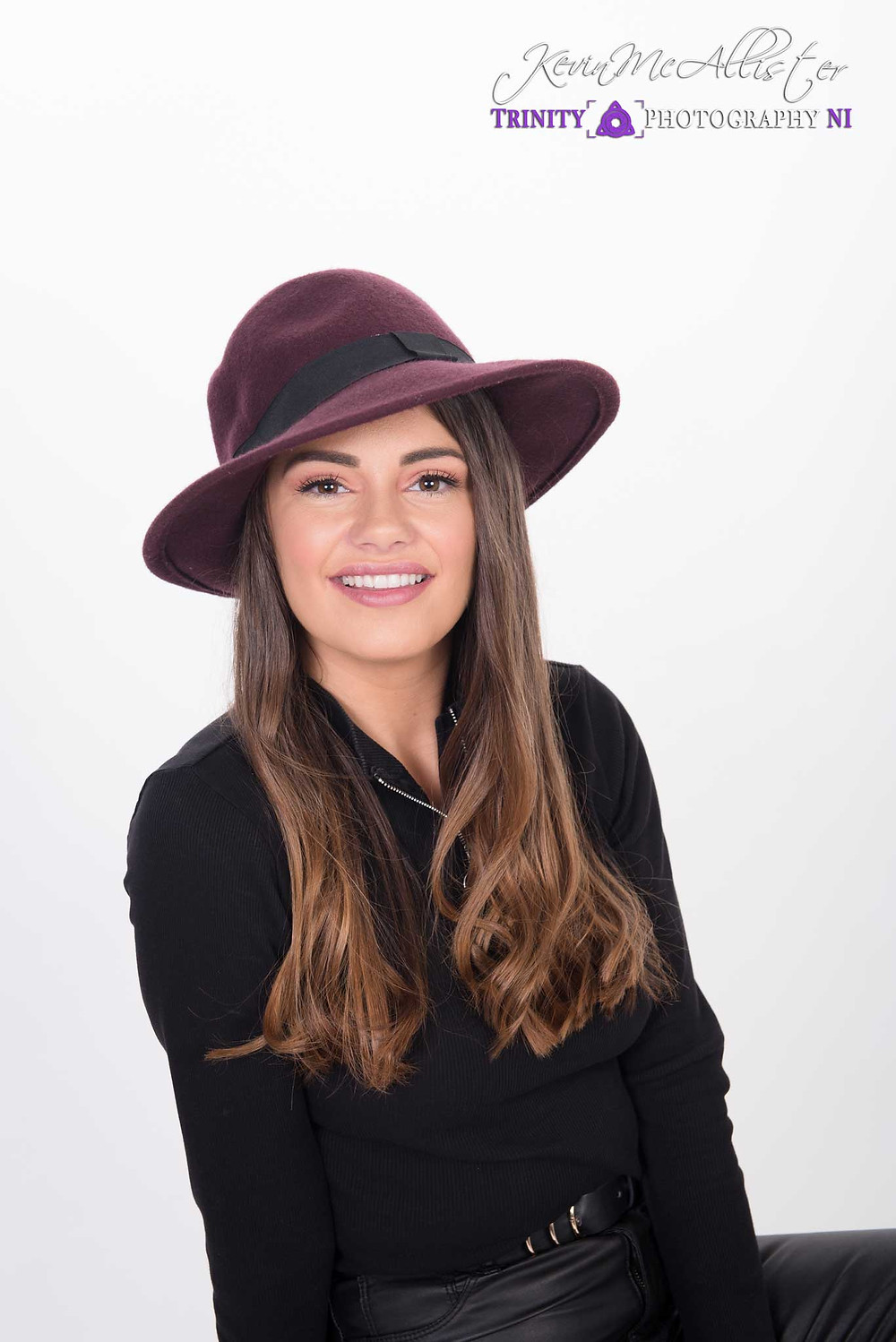 model in a burgundy hat with black outfit