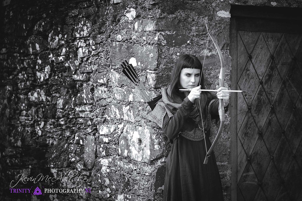 female medieval archer eyeing up her shot