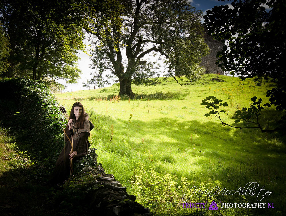 model dressed as an archer sitting on a wall in ireland