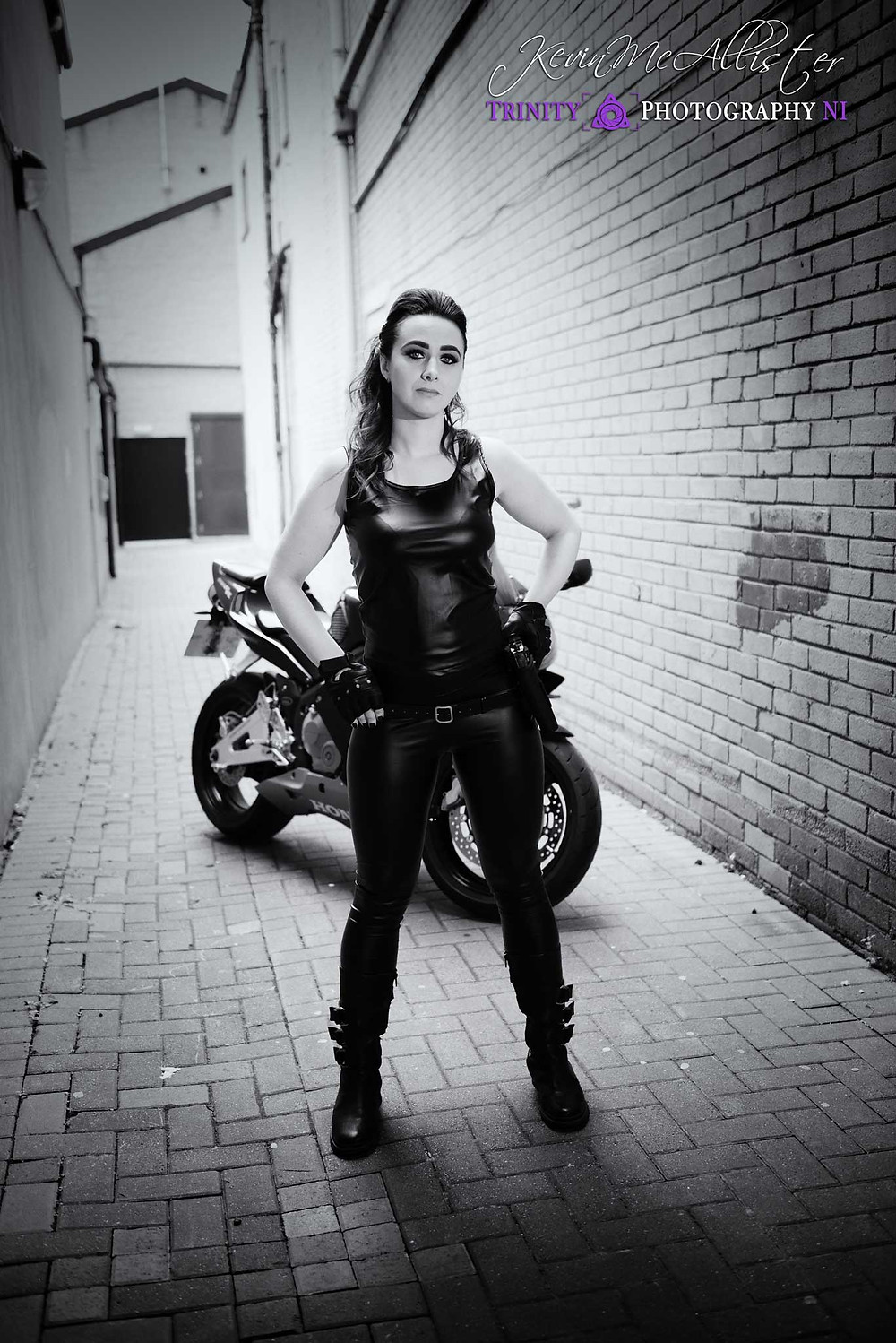 leather clad bike girl with gun and motorbike in the background.