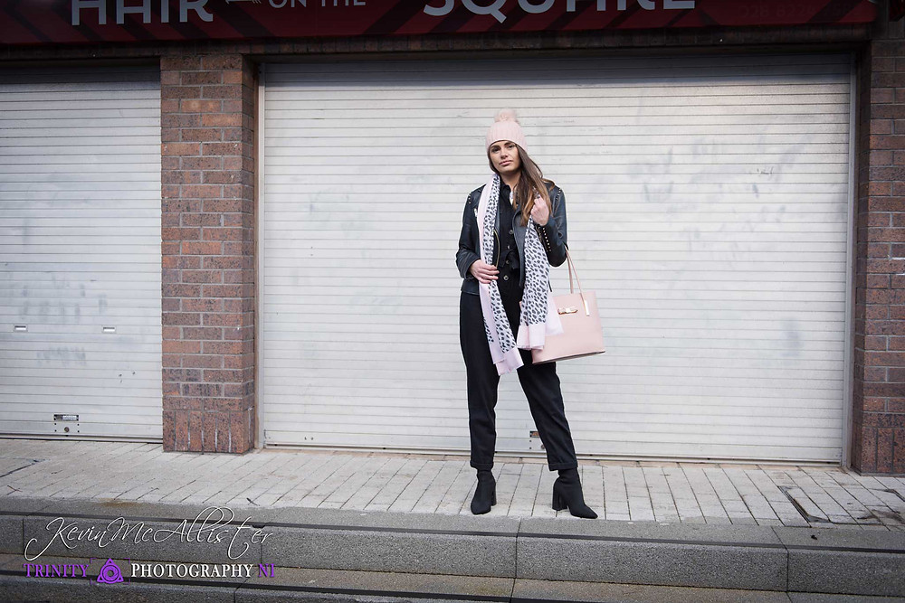 model with pink woolly hat  leopard print scarf and pink hand bag , urban location