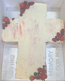 A cross cake with clusters of fruit , ca