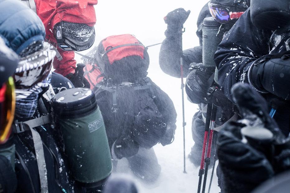 photographie d'aventure : un groupe de personne en hiver en tempete
