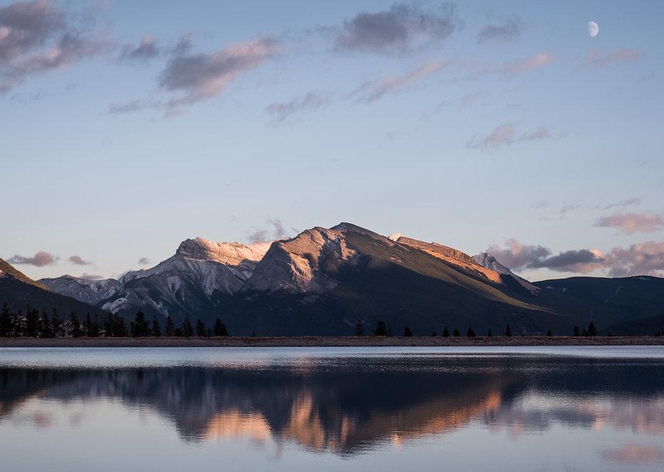 photographie d'une montagne au couché de soleil avec la lune au bord d'un lac
