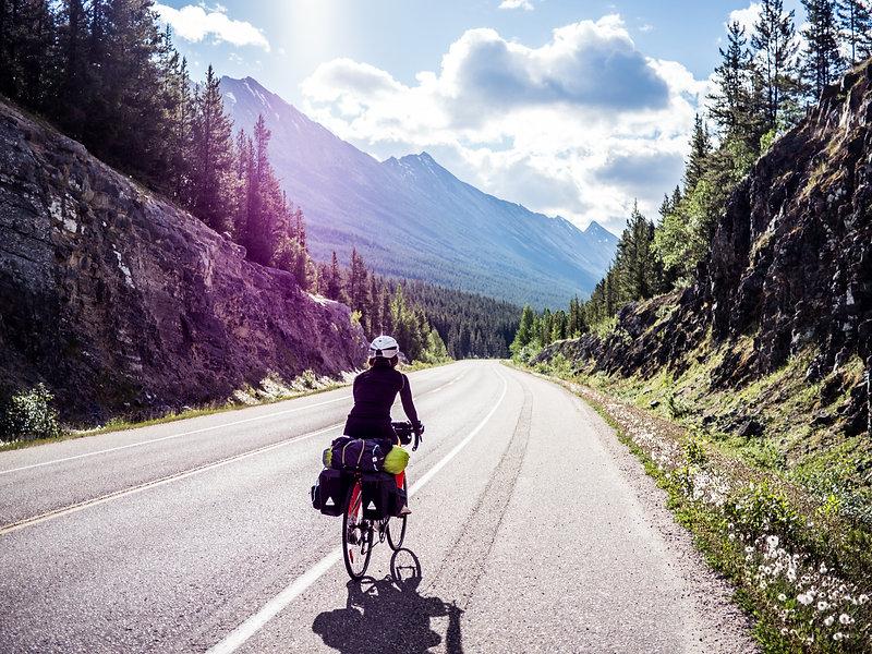 photographie d'aventure : une fille à vélo dans les montagnes canadiennes