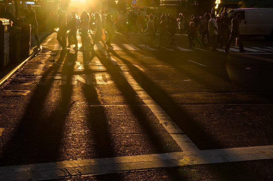 Photographie urbaine : des gens traversent la rue à New york au coucher de soleil