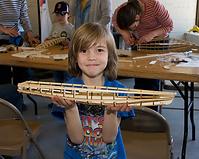 Enfant qui tient une maquette de bateau à voile dans les mains