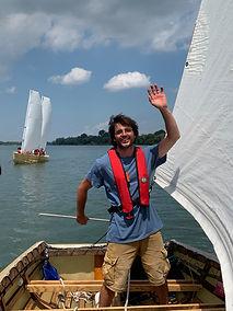 un homme fait un salut à la caméra depuis un bateau à voile