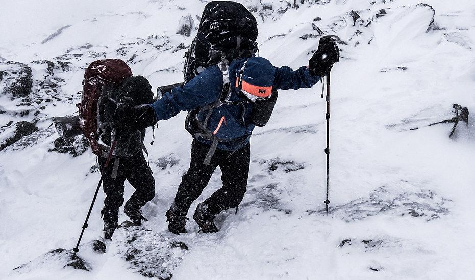 photographie d'aventure : deux personnes marchent en hive en montagne