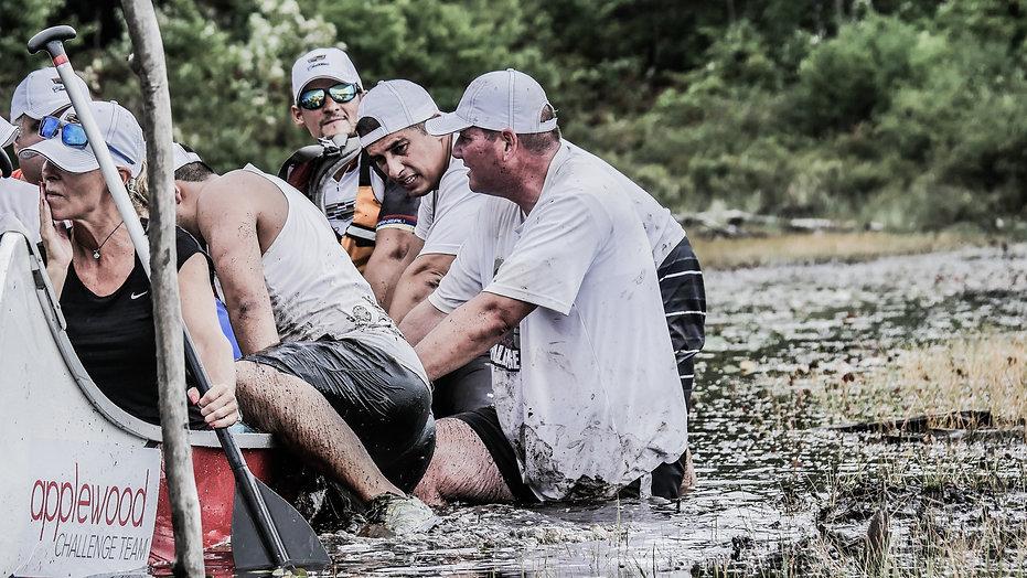 photogahie d'aventure : une équpe pagaye en canoe sur une rivière au canada