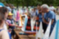 2 personnes inspectent des maquettes de bateaux à voile lors d'un concours