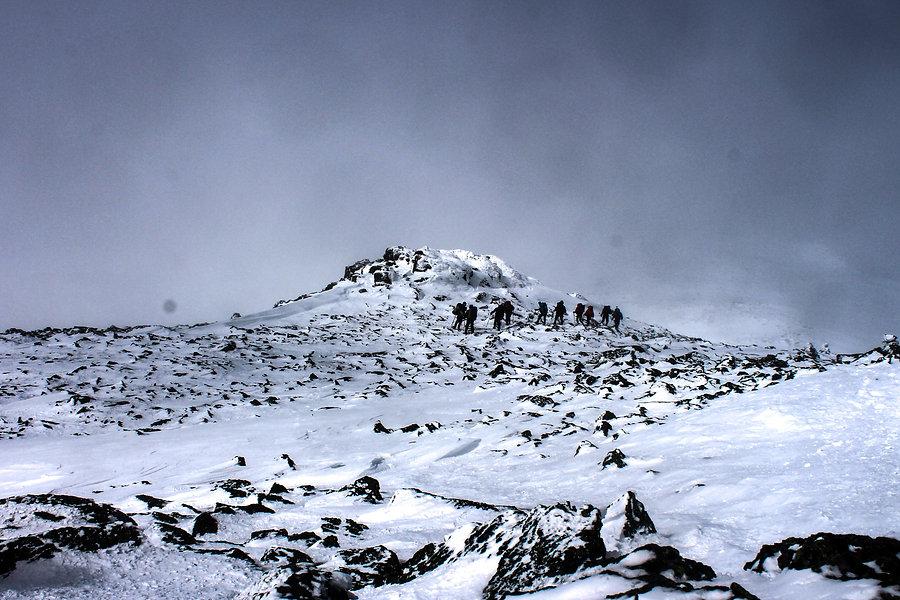 photographie d'aventure : une équipe monte une montagne eneigée en hiver