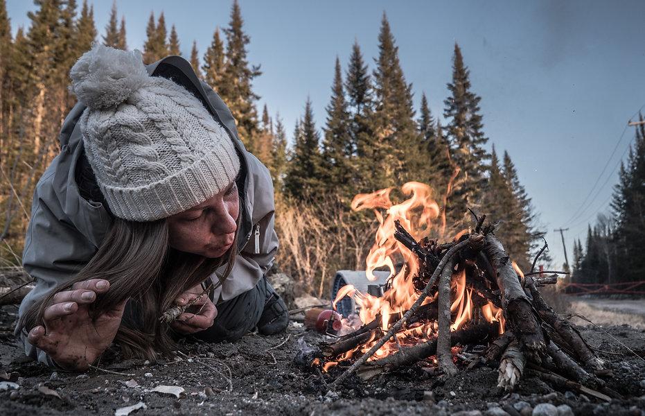 photographie d'aventure : une fill souffle su un feu dans les bois