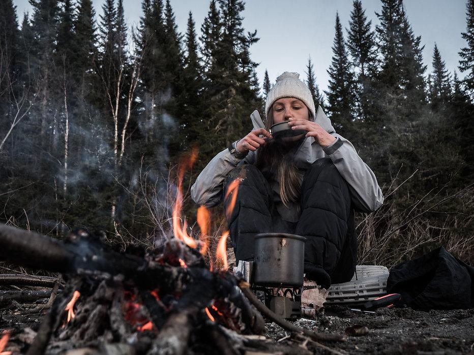 photographie d'aventure : une fille bois une soupe au bord d'un feu dans la forêt