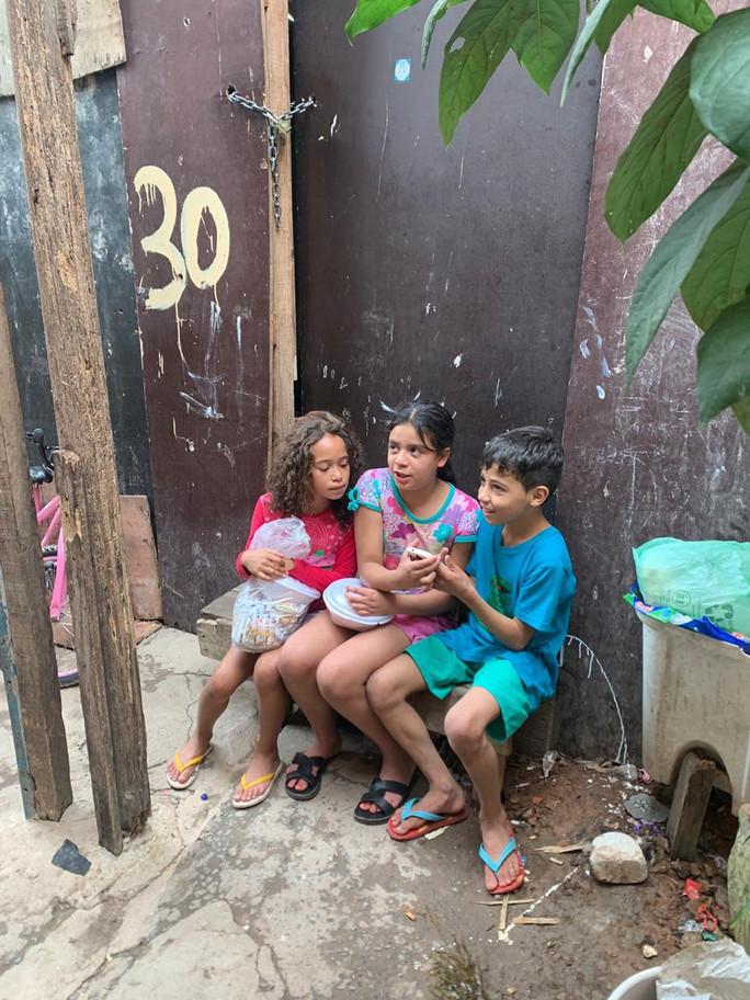 Crianças de Paraisópolis com as roupas que receberam de doação