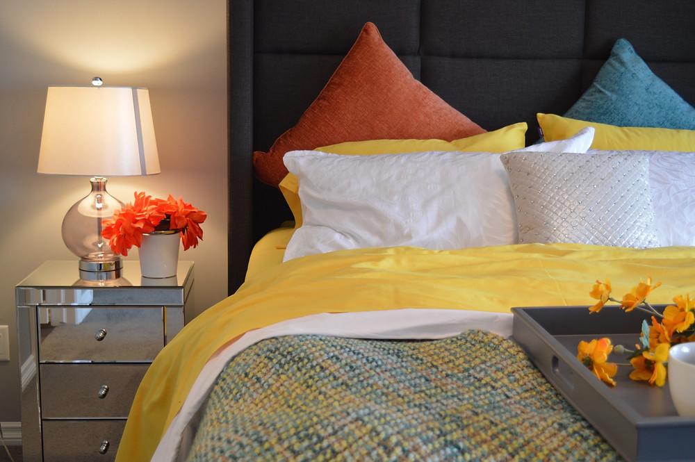Dormitório Casal Cama de Casal Mesa de Cabeceira Espelhada com Abajur Iluminação Aconchegante Quente Roupa de Cama Amarela branca e Laranja Bandeja de Café da Manha