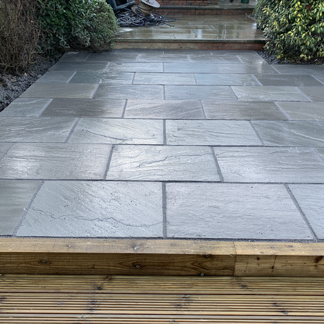 Grey Indian stone patio with wooden sleep edging.