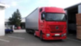 Roter LKW Transporter beim abliefern der Paletten und Gitterboxen