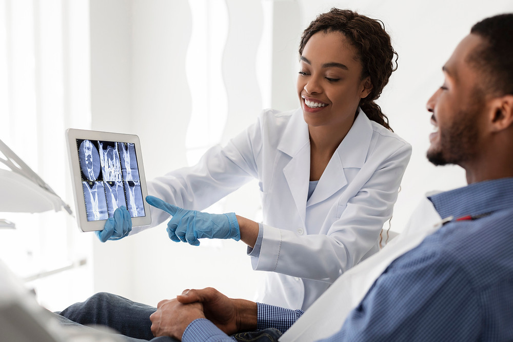 Dentist showing dental x-ray to patient
