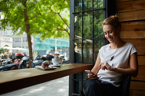 Charming woman with beautiful smile reading good news on mobile phone during rest in coffe