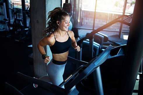 Top view of smiling woman exercising and training in the gym on treadmill running machine.