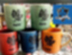 Maple leaf mugs, in orange, green, red, and blue