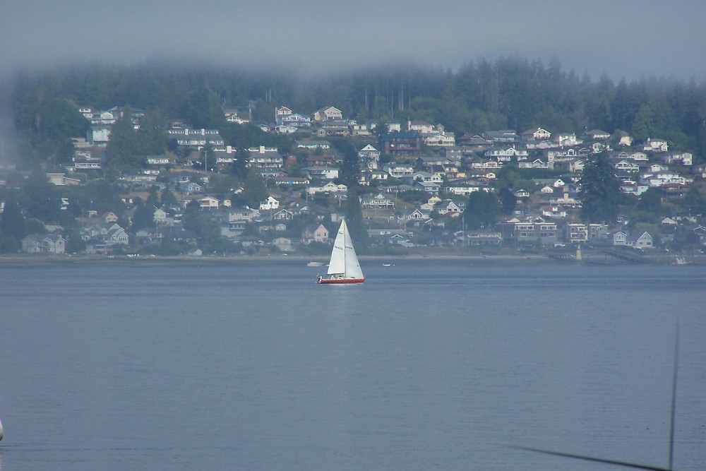 A sailboat passing the Town of Manchester, WA in the morning fog