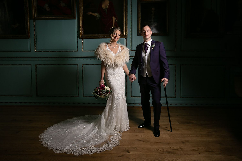 Photographed by John Knight | Bride in lace wedding dress and groom in purple suit standing in front of portraits at Bradbourne House, Kent wedding venue
