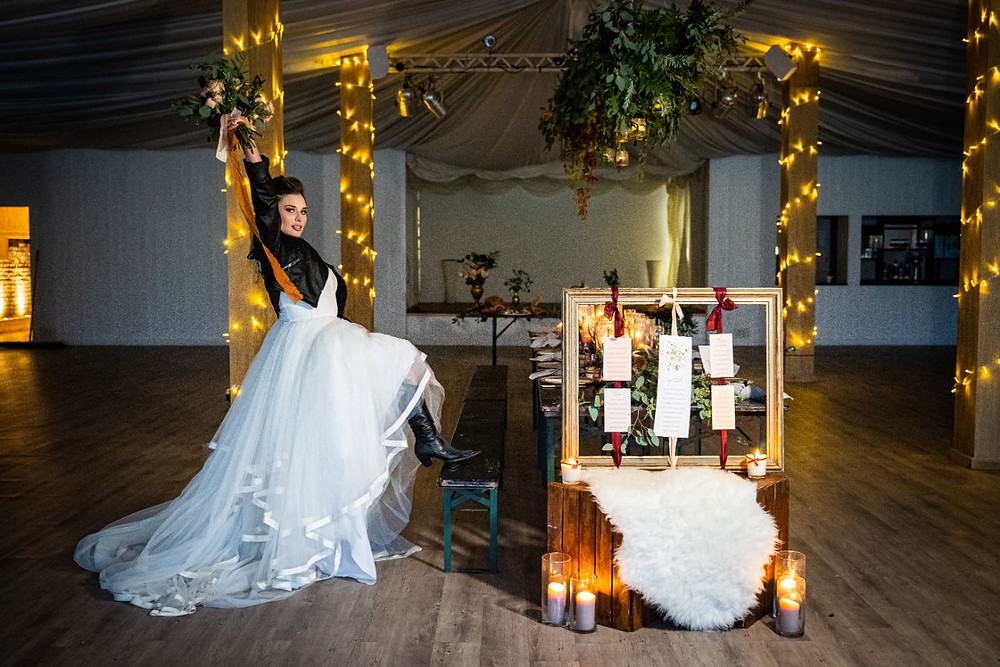James Grist Photography | Modern bride wearing leather jacket with foot on bench and holding flowers in the air