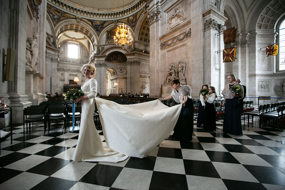 Bride walking across black and white chequered floor with bridesmaids