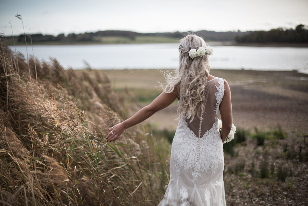Photographed by John Knight | Bride walking by reeds next to water