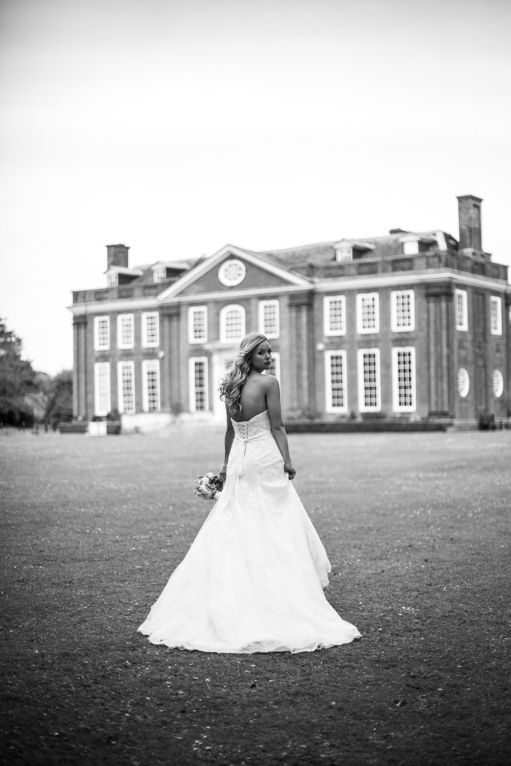 Photographed by John Knight | Black and white image of bride walking towards Bradbourne House, looking over her shoulder at the camera